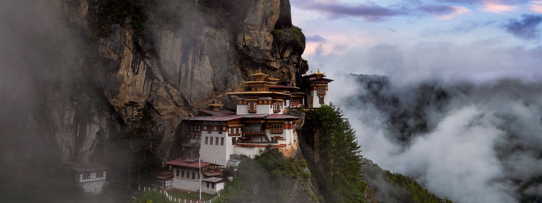 A beautiful twilight in Bhutan as soft fog swirls around the stunning structure of the Tigers Nest Monastery.